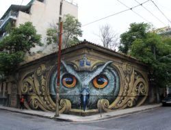 An owl dominates this street corner through this street art mural in Greece by Wild Drawing