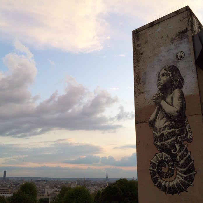 This large street art mural in Paris shows a hybrid child seahorse praying. Painting by Wild Drawing