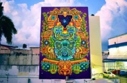 Areúz has covered the side of this big building with a street art mural that depicts animals, men and spirits in the ancient Mayan art style