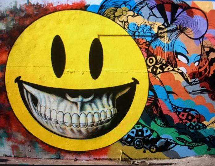 Ron English reminds us that the smiley face emoticon is based on a human face by showing a grinning human skull peeking out of the smiley's mouth in this colorful street art mural