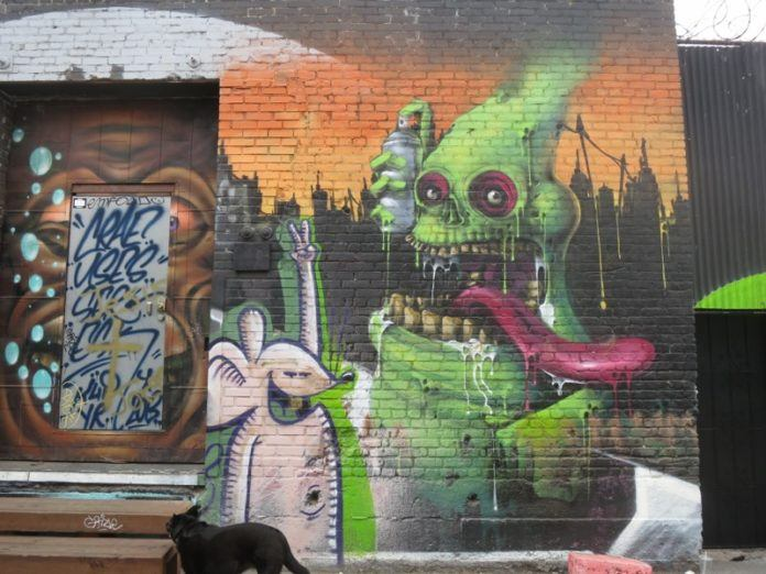 A skeleton Slimer holds a spray can in this street art mural in Los Angeles by K4P Crew