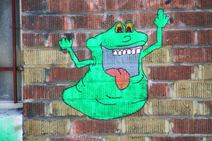 An anonymous street artist has painted the green ghost Slimer flipping off pedestrians in this cheeky graffiti piece