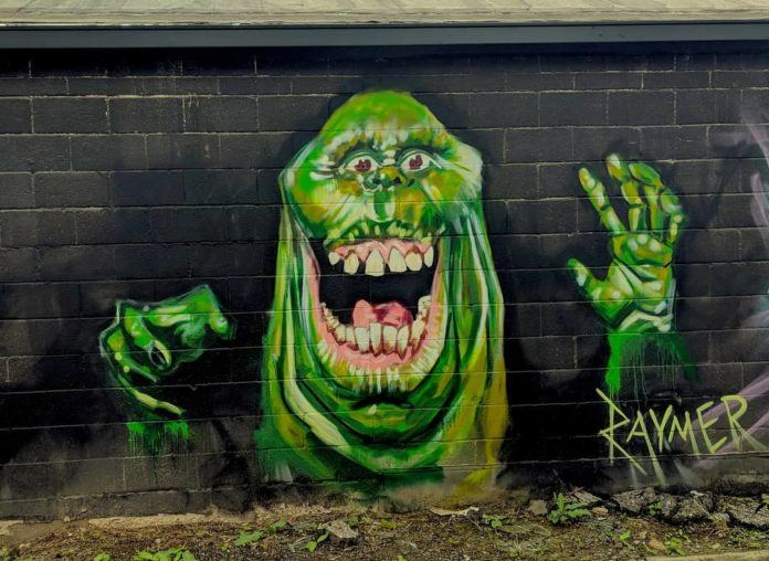 Street artist raymer has used light and dark shades of green spray paint to create contrast in this Slimer wall mural