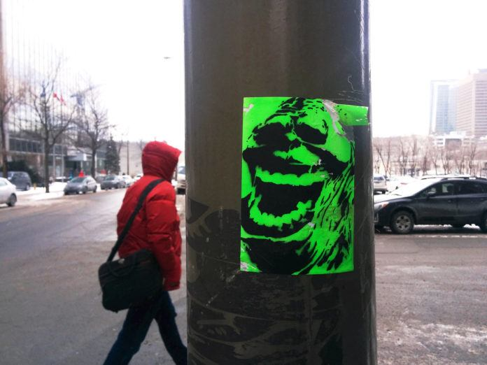 This stencilled Slimer sticker is a colorful street art work in the gray winter of Montréal
