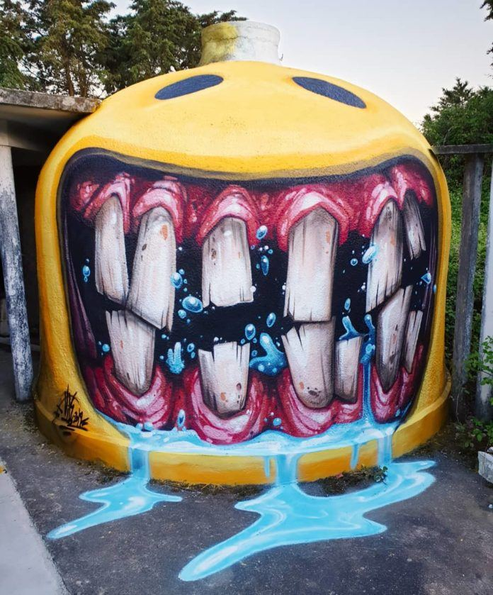 Street artist VILE has chosen a rounded surface for this crazy drooling happy face graffiti art work