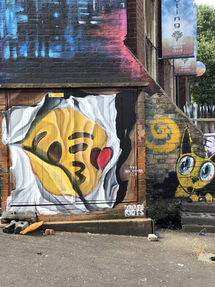 Street artist and musician Airborne Mark has painted a graffiti wall mural of a crumpled piece of paper with a giant winking kissy face emoji on it